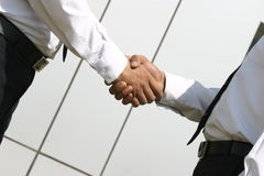 Shaking hands. Two Young executive shaking hands in front of a building Stock Images