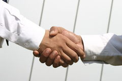 Shaking hands. Two Young executive shaking hands in front of a building Royalty Free Stock Photo