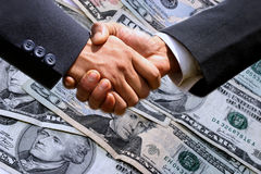 Shaking hands. Business man shaking hands with money in the background Royalty Free Stock Photography