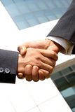 Shaking hands. Two young businessmen shaking hands in front of a building Royalty Free Stock Image