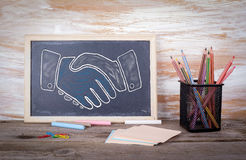 Shaking hands on a blackboard. Old wooden table with texture Stock Photography