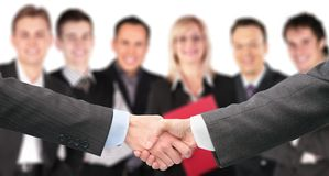 Shaking hands and business group out of focus Royalty Free Stock Photo