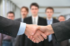 Shaking hands and business team Royalty Free Stock Image