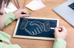 Shaking hands. Chalkboard on wooden office desk Stock Photos