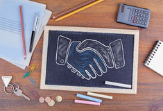 Shaking hands. Chalkboard on wooden office desk Royalty Free Stock Photos