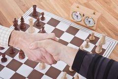 Shaking hands by a chess match Stock Photo