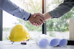 Shaking hands of collaboration, Construction engineering or architect discuss a blueprint while checking information on drawing royalty free stock image