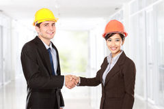 Shaking hands at construction site Stock Image