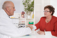 Shaking hands at doctor with senior patient. Stock Photo