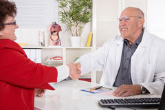 Shaking hands at doctors office with his senior patient. Stock Photos