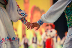 Shaking hands ethnic folklore people. And dancing royalty free stock image