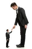 Shaking Hands With för jätte- affärsman liten man Royaltyfria Bilder