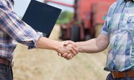 Shaking hands on farmland. Close up of two men in plaid shirts shaking hands on the farmland. Combine harvester working in background Royalty Free Stock Photos