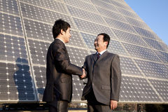 Shaking hands in front of solar panels Royalty Free Stock Images