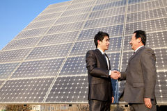 Shaking hands in front of solar panels Royalty Free Stock Photo