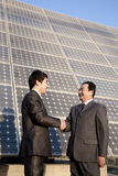 Shaking hands in front of solar panels Stock Photography