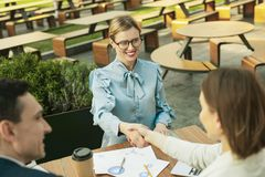Happy joyful lady smiling when shaking hands royalty free stock photo