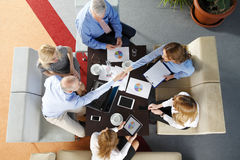 Shaking hands. High angle view of business team sitting around the desk and shaking hands. Businesswomen and businessmen sitting around conference table. Group Royalty Free Stock Photos