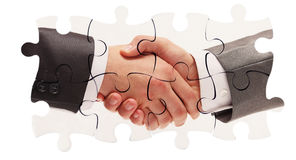 Shaking hands inside puzzle pieces Stock Images