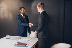 Shaking hands on a new merger. Two young businessmen standing in a modern boardroom shaking hands together after a successful negotiation Royalty Free Stock Photos