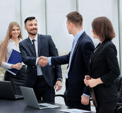 Shaking hands in the office at the beginning of the working day Stock Photo