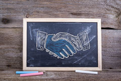 Shaking hands. Old wooden background with texture and chalk blac Stock Photo