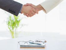 Shaking hands over eye glasses and diary after business meeting Stock Photo