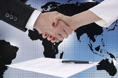 Shaking hands over map of the world Stock Images