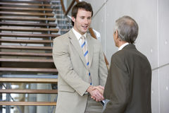 Shaking hands on a staircase Stock Photography