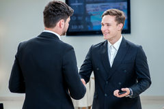 Shaking hands. Two confident businessman shaking their hands and Royalty Free Stock Image