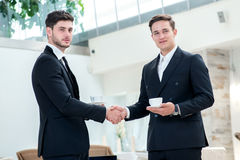 Shaking hands. Two other businessman drinking coffee and talking Stock Photos