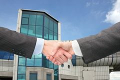 Shaking hands with wrists near blue building. On sunny day Stock Image
