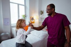 Pleasant pediatrician shaking little hand of cute appealing girl royalty free stock photos