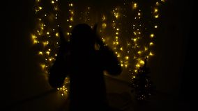 Dancing girl silhouette and twinkling garlands. Shaking movements in the dark. Raving female person with garlands on background. Concept of house  New Year stock video
