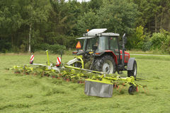 Shaking of the mown grass with red tractor with Ted Stock Photos
