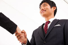 Shaking young Asian business man. Royalty Free Stock Photo