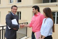 Shakings de los pares con agente inmobiliario Imagen de archivo libre de regalías