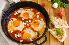 Shakshouka, plato de los huevos escalfados en una salsa de tomates, chile, cebollas en la cacerola imagenes de archivo