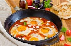 Shakshouka, plato de los huevos escalfados en una salsa de tomates, chile, cebollas en la cacerola fotografía de archivo libre de regalías
