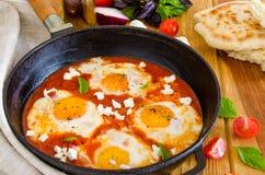 Shakshouka, plato de los huevos escalfados en una salsa de tomates, chile, cebollas en la cacerola foto de archivo libre de regalías