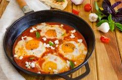Shakshouka, plato de los huevos escalfados en una salsa de tomates, chile, cebollas en la cacerola imagen de archivo