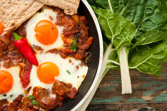 Shakshouka. Or shakshuka is a dish of eggs poached in a sauce of tomatoes, chili peppers, and onions, spiced with cumin. This recipe includes swiss chard leaves Royalty Free Stock Images