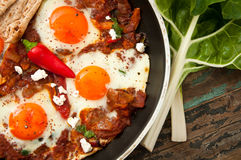 Shakshouka. Or shakshuka is a dish of eggs poached in a sauce of tomatoes, chili peppers, and onions, spiced with cumin. This recipe includes swiss chard leaves Royalty Free Stock Photography