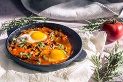 Shakshuka вкусное блюдо яя, зажаренное в соусе томатов, горячего перца, лука и приправ на черном лотке чугуна стоковые фото