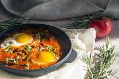 Shakshuka вкусное блюдо яя, зажаренное в соусе томатов, горячего перца, лука и приправ на черном лотке чугуна стоковое изображение rf