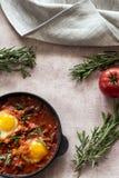 Shakshuka вкусное блюдо яя, зажаренное в соусе томатов, горячего перца, лука и приправ на черном лотке чугуна стоковая фотография