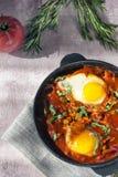 Shakshuka вкусное блюдо яя, зажаренное в соусе томатов, горячего перца, лука и приправ на черном лотке чугуна Томат стоковые фотографии rf
