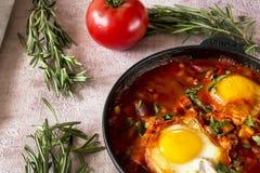 Shakshuka вкусное блюдо яя, зажаренное в соусе томатов, горячего перца, лука и приправ на черном лотке чугуна Томат стоковая фотография