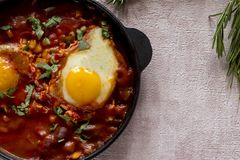 Shakshuka вкусное блюдо яя, зажаренное в соусе томатов, горячего перца, лука и приправ на черном лотке чугуна Томат стоковая фотография rf