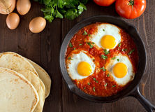 Shakshuka. With eggs, tomato, and parsley in a cast iron pan Royalty Free Stock Photo